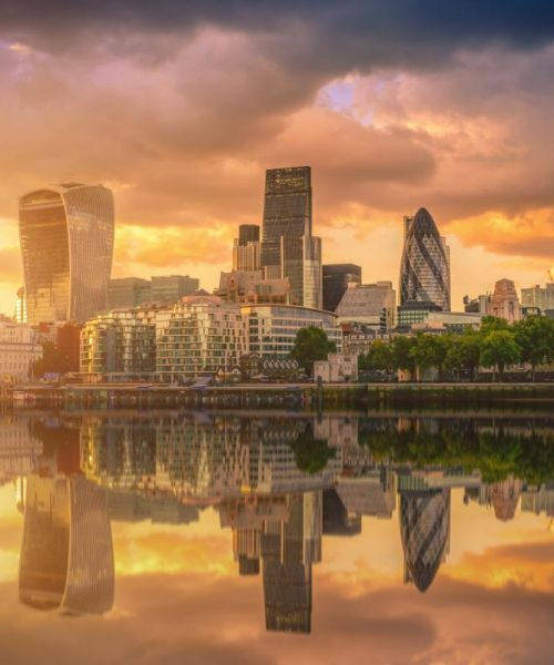Skyscrapers of the City of London over the Thames river at sunset in England.